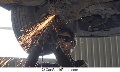Mechanic guy with glasses cutting worn automobile part with grinder in garage