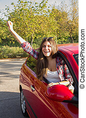 Portrait of happy young woman going on a road trip leaning out of window of the red car.