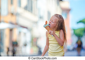 Adorable little girl eating ice-cream outdoors at summer in...