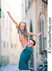 Adorable little girl and happy dad during summer italian vacation in empty narrow street