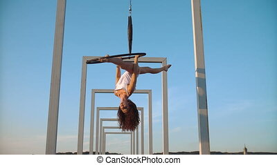 Air gymnastics woman performs acrobatics tricks on aerial...
