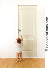 Baby in front of door - Baby in front of a closed door,...