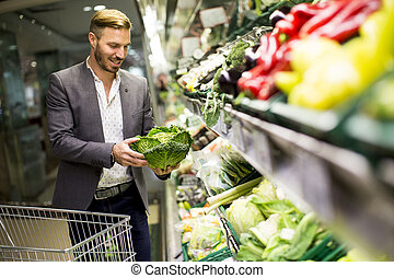 Man in supermarket - Young man buying vegetables in the...