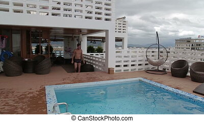 Man jumping in a roof top luxury swimming pool.