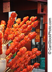 Candied Strawberries on a stick at food market in Beijing in...