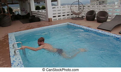 Man swimming in a roof top luxury swimming pool. coming out of the pool and goodbye