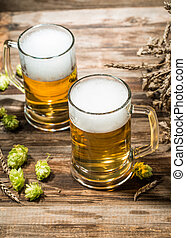 Two mugs of beer on wooden table with hops
