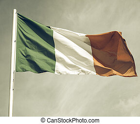 Vintage looking Irish flag over a blue sky background