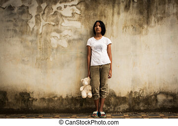 Blurry of sad asian girl alone with white bear near old wall...