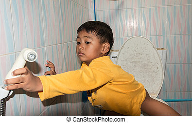 cute child little asian boy defecate in toilet