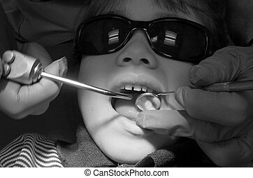Child patient having her teeth examined by specialist...