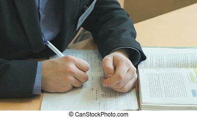 Schoolboy writes text in exercise book on lesson - Schoolboy...