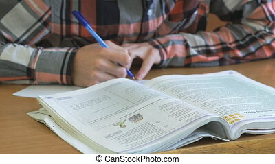 Adolescent writes the text in notebook on lesson -...