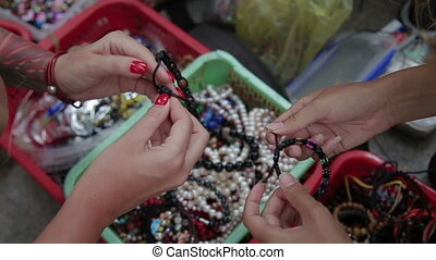 Woman looking at the beads - Female hands choosing a...