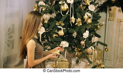 Beautiful woman decorate Christmas tree with cute toys