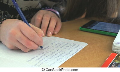 Pupil writes the text on white sheet of paper