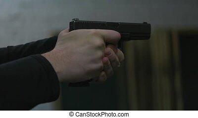 man shoots a gun at shooting range close up.