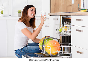 Woman Taking Drinking Glass From Dishwasher - Young Woman...