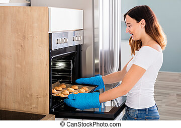 Woman Placing Tray Of Cookies In Oven