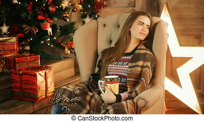 Woman sitting in chair and drinking beverage. New year or...