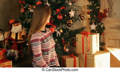 Beautiful woman in Christmas taking gift boxes near...