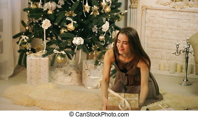 Beautiful woman hiding gifts under Christmas tree