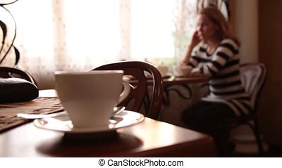 Pretty young woman sitting at cafe drinking tea or coffe and smiling