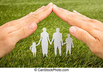Person Hand Protecting Family Papercut - High Angle View Of...