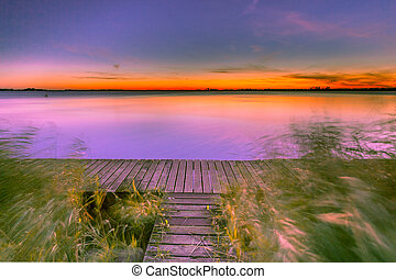 Long Exposure Image of Purple Sunset over Boardwalk on the shore of a Lake