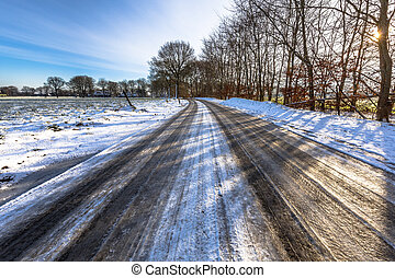 Black ice on a countryside road - Glazed ice on a road in...