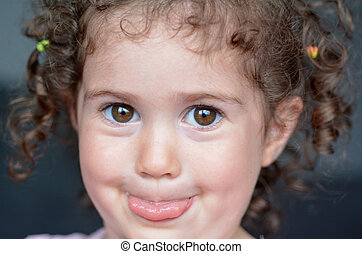 Child sticking a tongue out - Curly child (girl age 02)...