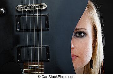 Blonde woman holding electric guitar, black background -...