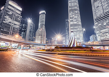 modern shanghai at night - light trails on the roundabout...