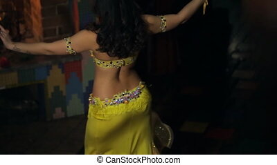 Beautiful brunette shows belly dance back view. Beauty in...