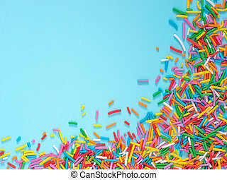 Border frame of colorful sprinkles on blue background with...