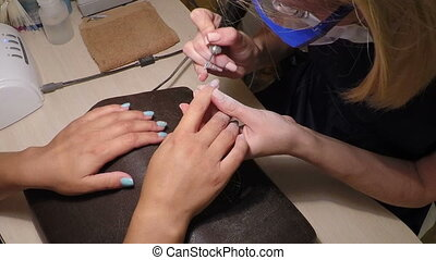 Master makes manicure removes the remnants - manicurist...