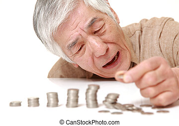 stack of coins collapsed when senior Japanese man put a coin...