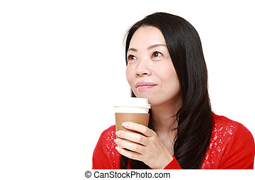 Japanese woman takes a coffee break - studio shot of...