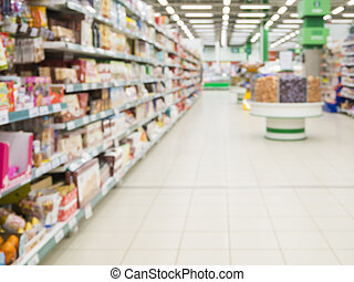 Abstract blurred supermarket aisle with colorful shelves as...