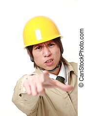 young Japanese construction worker scolding - studio shot of...