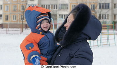 Baby in his mother's arms in the park in winter. They warmly dressed, mother talking to her son. Handsome boy about a year. Winter lifestyle concept.