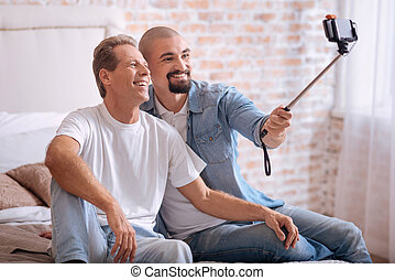 Smiling non-traditional couple taking selfie in the bedroom...