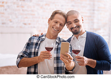 Delighted non-traditional couple drinking wine and taking...