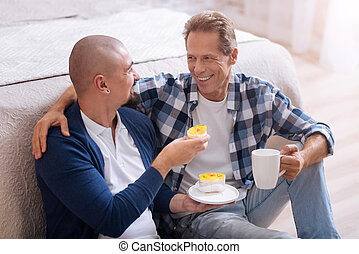 Cheerful non-traditional couple eating bakery together - It...