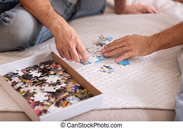 Nice box with puzzles lying on the bed - We putting pieces...