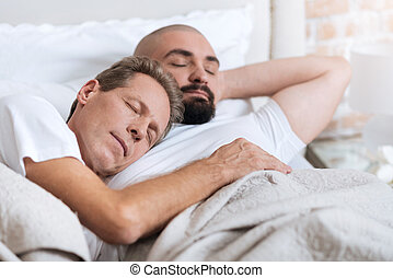 Pleasant non-traditional couple sleeping in the one bed - We...
