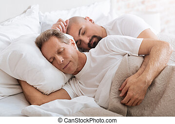 Positive delighted non-traditional couple sleeping together...