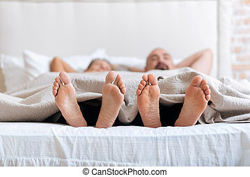 Pleasant non-traditional couple showing their feet - We...