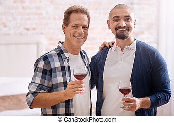 Smiling non-traditional couple drinking wine at home - We...