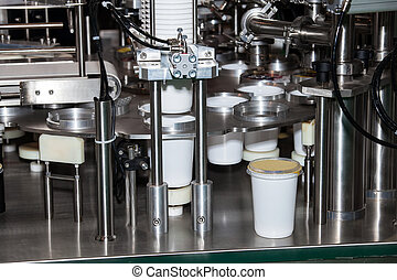 Filling and sealing machine in preformed plastic cups with...